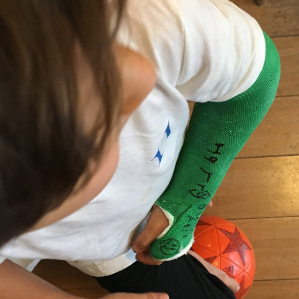 Boy in a green arm cast with his foot on a soccer ball