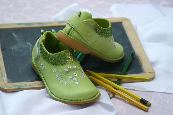 Image of children's green shoes sitting atop a toy blackboard and some pencils