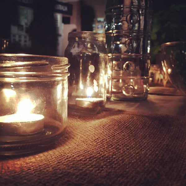 Image of tealights in jars on a table in a dark room
