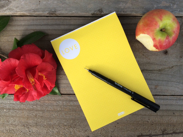 Desk with a notepad, pen, apple and a flower on it