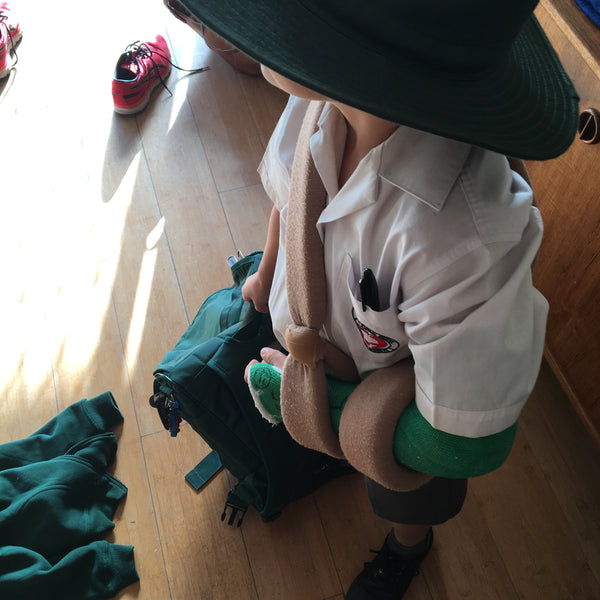 Child in a school uniform holding a school bag with a green plaster cast and sling
