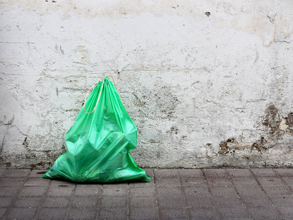 Image of green rubbish bag against a wall