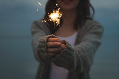 Woman holding a sparkler with both hands