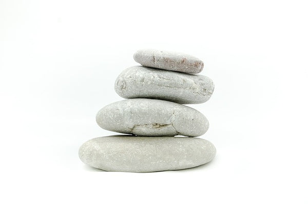 Image of stones stacked on top of one another against a white background