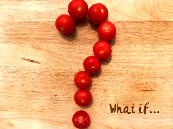 "Question mark made out of cherry tomatoes on a wooden board, with the question ""What if..."""