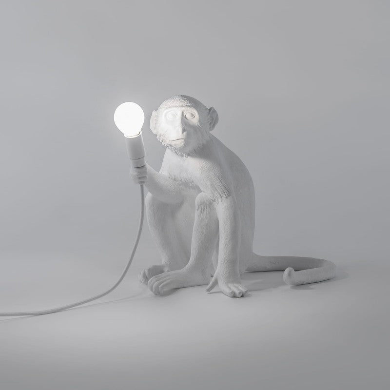 sitting down seletti monkey lamp in white holding ligh bulb