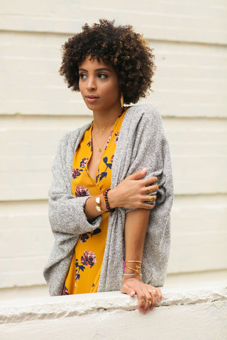 Girl bunching up her cardigan showing off an assortment of jewelry