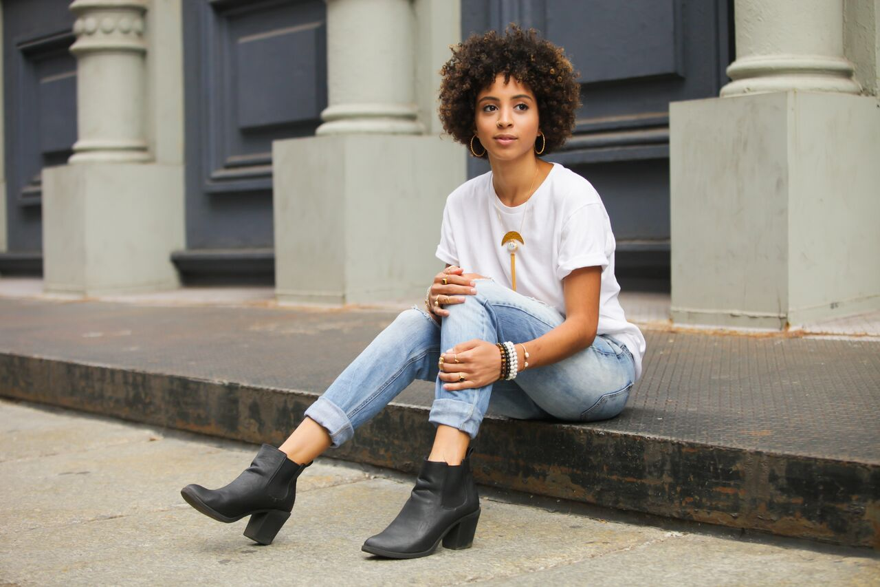 Girl sitting on a curb in ripped jeans, t-shirt, and a variety of jewelry