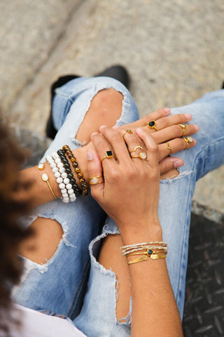 Close up shot of girl wearing an assortment of rings, healing stone bracelets, and other gold bracelets.