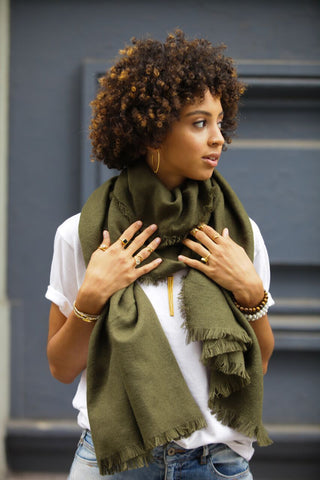 Girl holding onto olive scarf showcasing a bunch of stacking rings and bracelets
