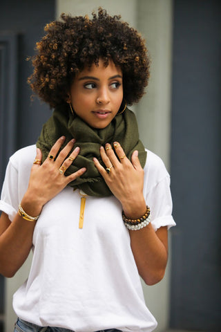 Girl holding onto olive scarf wearing an assortment of stacking rings and bracelets
