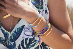 Detail Shot of Girl Wearing Beaded Bracelets & Gold Bracelets