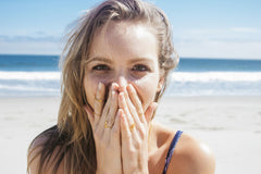 Girl Covering Her Mouth Wearing Lots of Rings & Beach In The Background