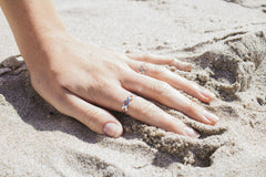 Detail Shot Of A Hand In Sand Wearing A Lot Of Rings