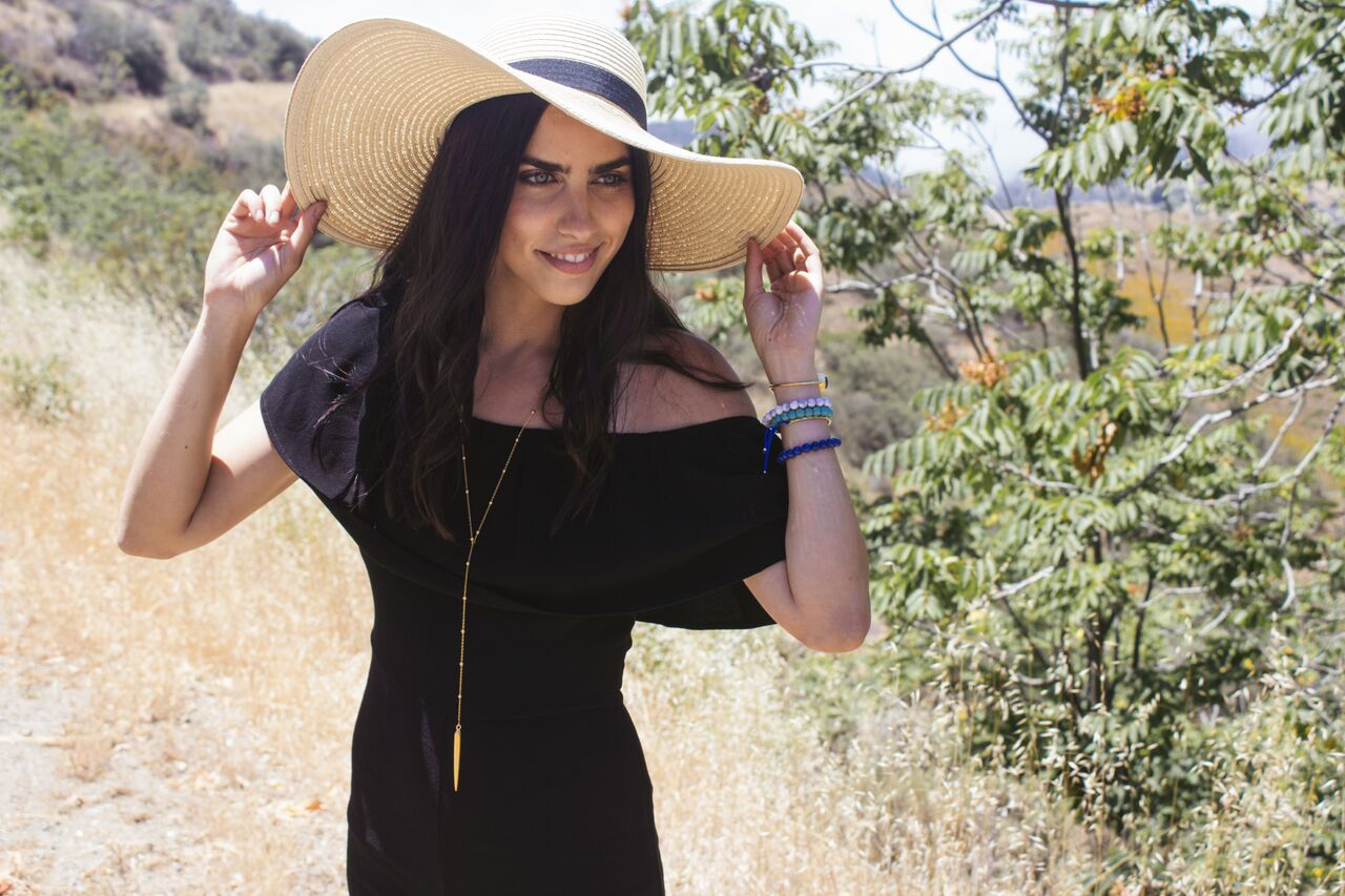 Girl In Large Sun Hat & Black Off The Shoulder Romper & Wearing Jewelry