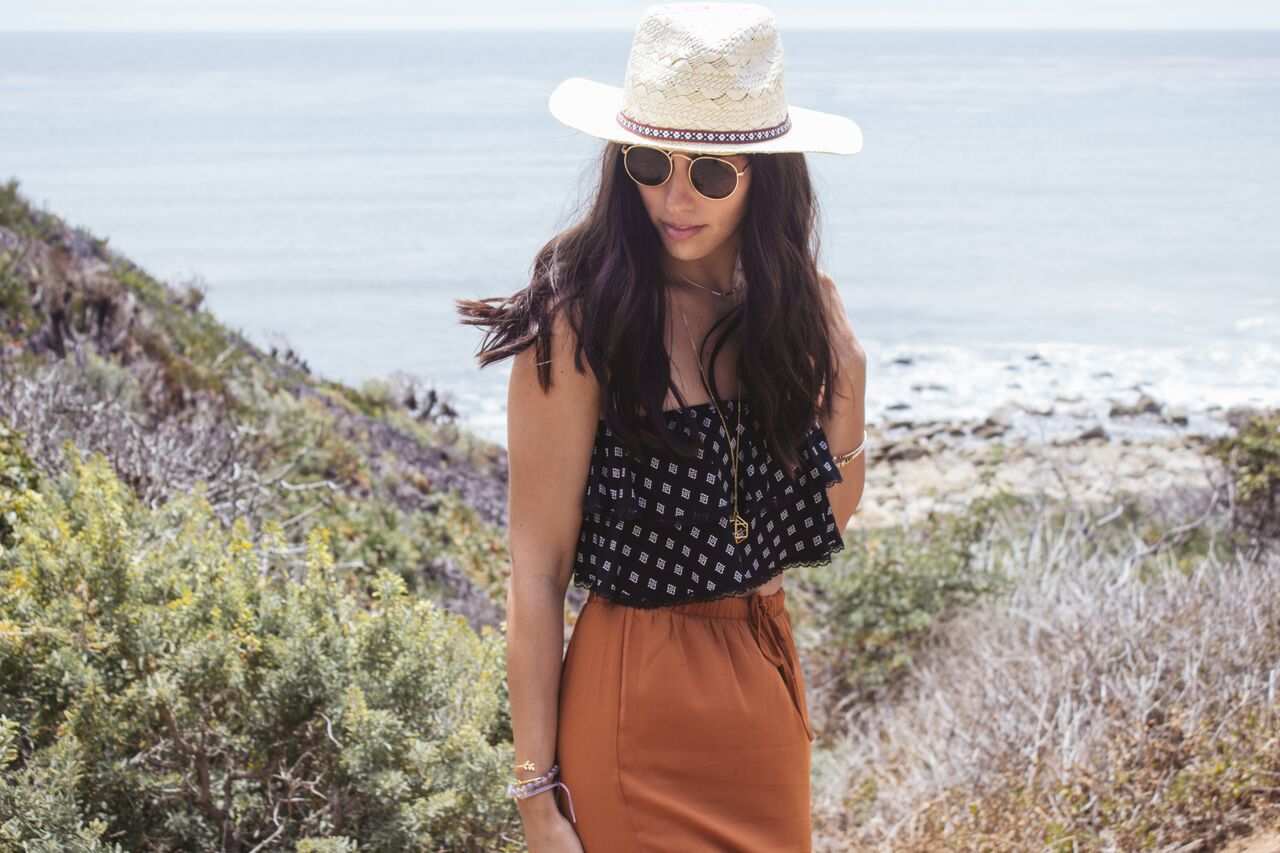 Girl Standing With Hat, Sunglasses, & Jewelry With Beach In Background