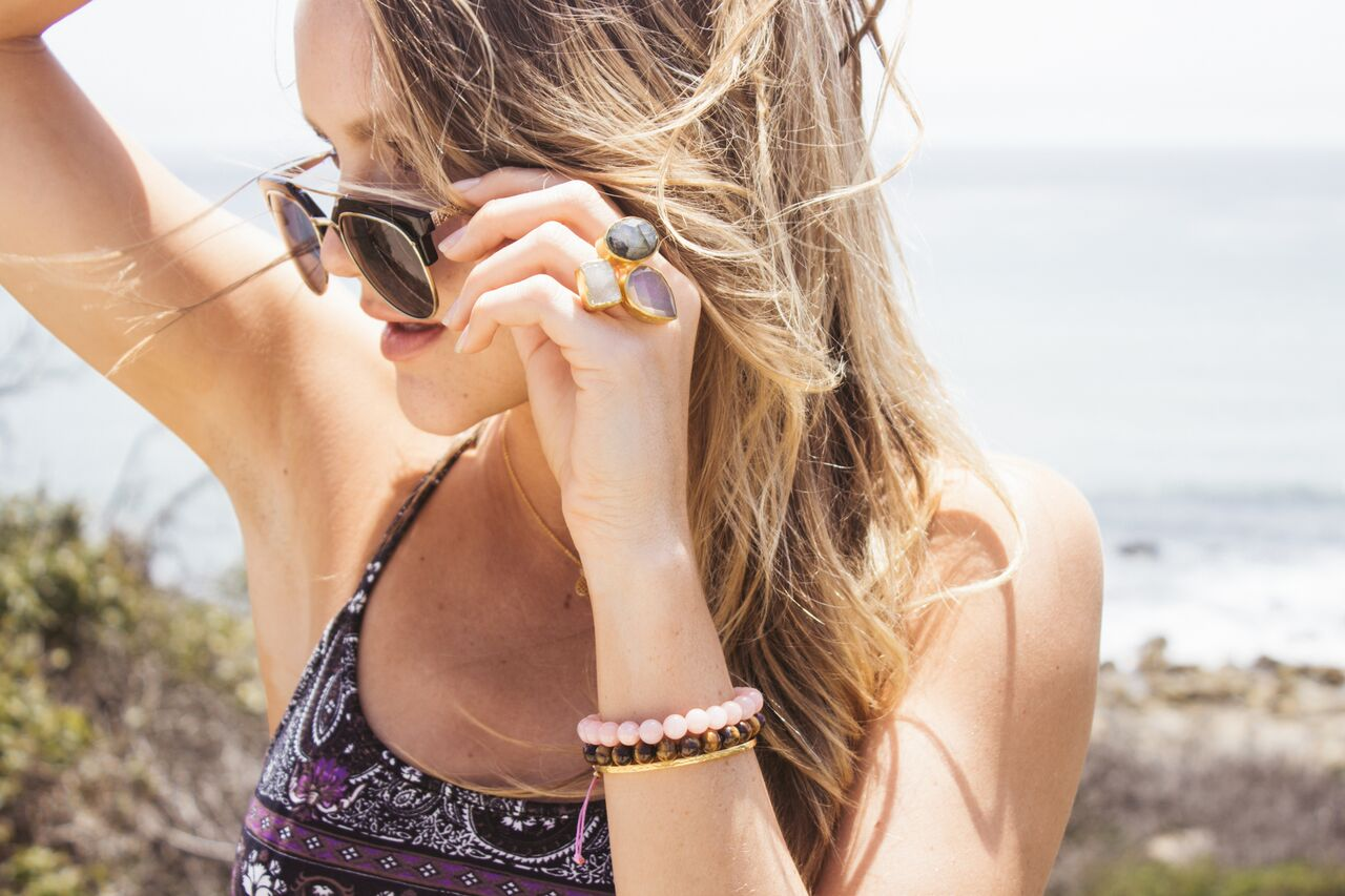 Girl Peering Down Her Sunglasses Wearing Ring & Healing Stone Bracelets
