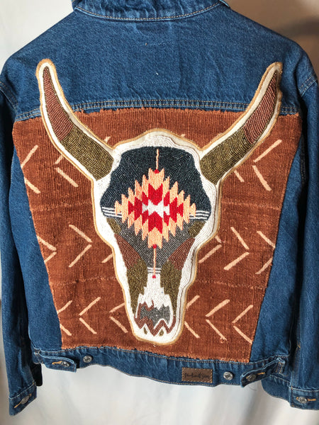 Denim jacket with added hand beaded cow skull on African Mud cloth