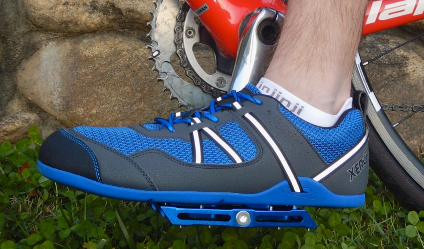 Side view of a Blue Catalyst Pedal and Xero Prio athletic shoe with grass and stonework in the background.