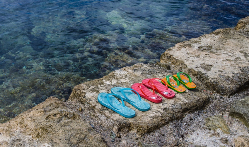 Several pairs of flip-flops sitting side by side on a stone wall overlooking water