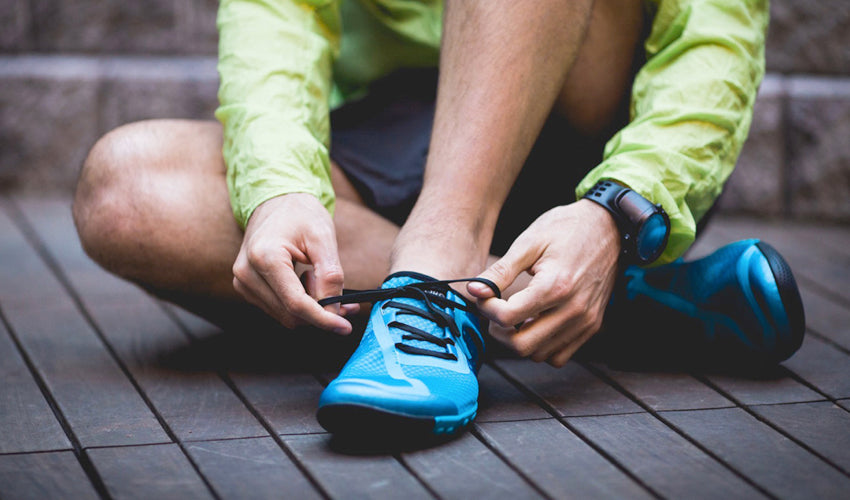 Runner putting on tapering toe box minimalist shoes