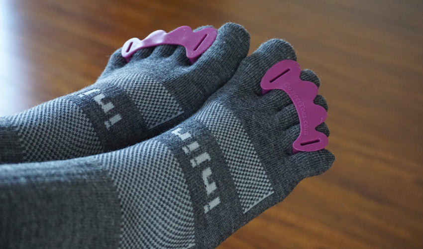 A close-up view of Correct Toes Plum toe spacers and Injinji crew toe socks with a hardwood floor in the background