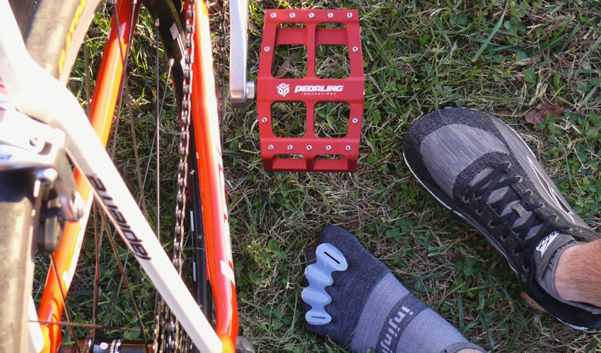 Top-down view of Catalyst Pedals, Correct Toes toe spacers, Injinji toe socks, and foot-shaped athletic shoes