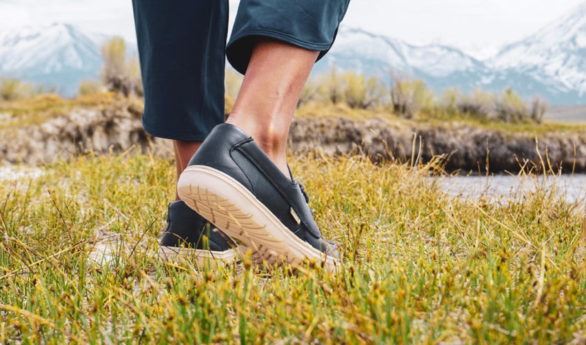 A person standing in a grassy meadow and wearing Lems Mariner Navy boat shoes