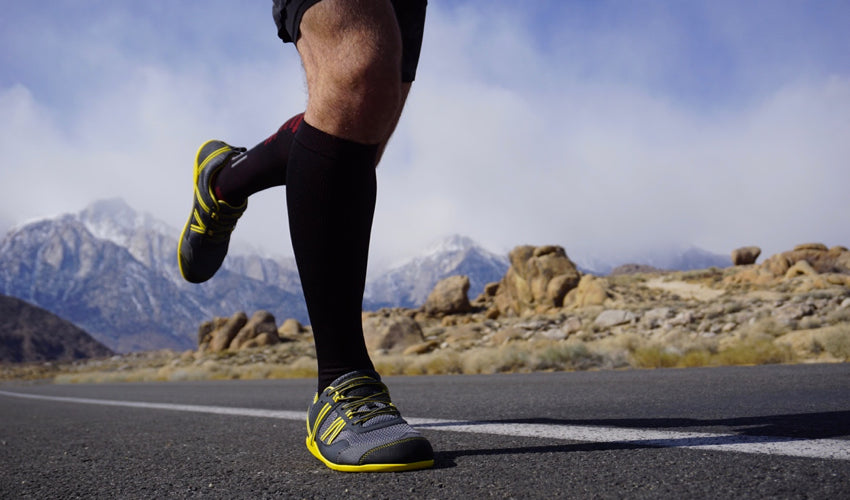 A road runner, mid-stride, wearing Xero Prio shoes and Injinji compression toe socks