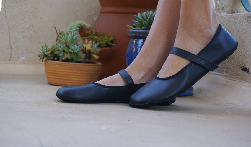 A side view of a pair of Ahinsa Ananda Ballerina shoes in Black with several potted plants in the background