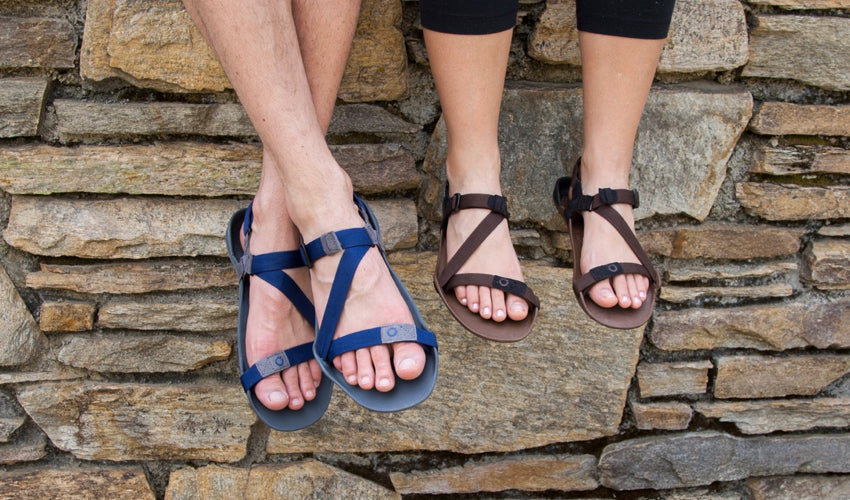 A couple wearing Xero sandals and sitting next to each other on a stone wall