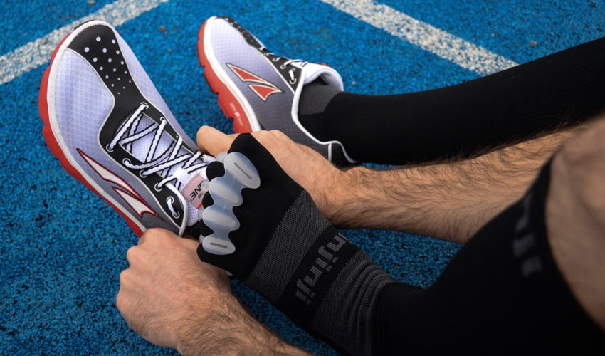 An athlete seated on a running tracking putting on a pair of Correct Toes and Altra athletic shoes