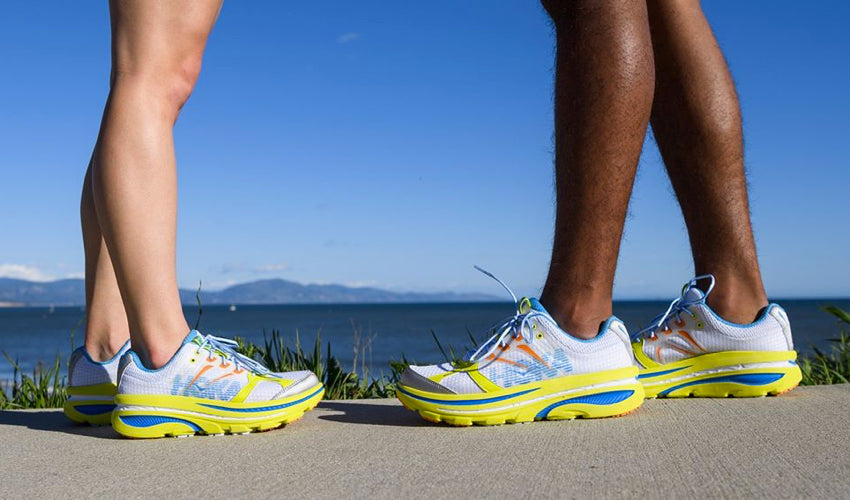 Stationary runners facing each other and wearing the same model of Hoka maximalist athletic shoes
