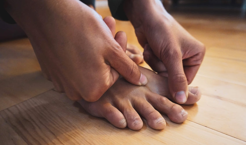 A barefooted person performing a bunion correction exercise