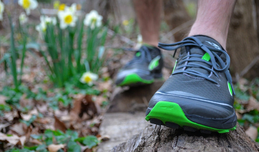 Runner wearing Altra athletic shoes balancing on a log in springtime conditions
