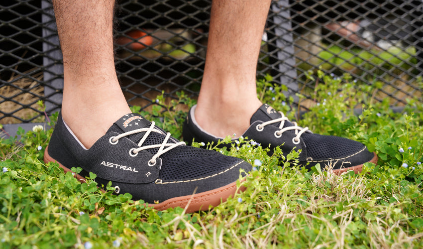 A man wearing a pair of Astral Hemp Porter 2.0 deck shoes while standing in some tall grass