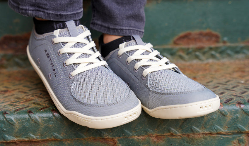 Person wearing Astral Loyak Shoes in Gray/White and standing on a green, rusty stair step