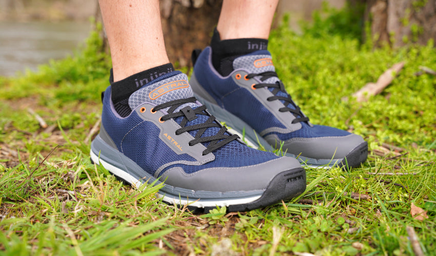 Athlete standing in front of trees and a river wearing Astral TR1 Mesh trail shoes