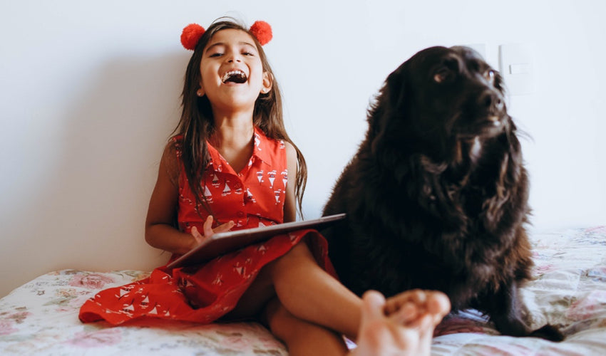 Young girl in a red dress laughing and playing with a tablet with a pet dog at her side
