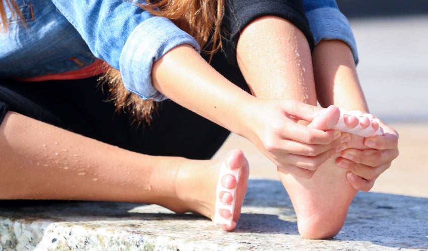 Young girl putting on a pair of Correct Toes Original toe spacers