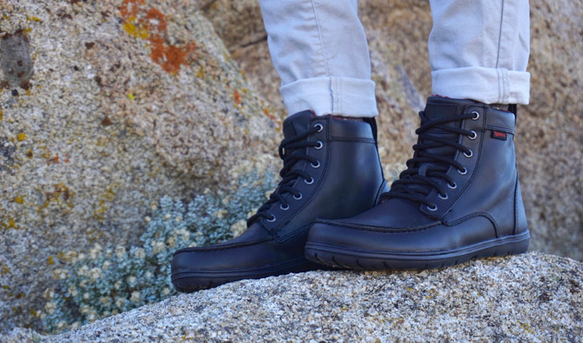Side view of the Lems Boulder Boot in Leather Raven set against a colorful rock backdrop