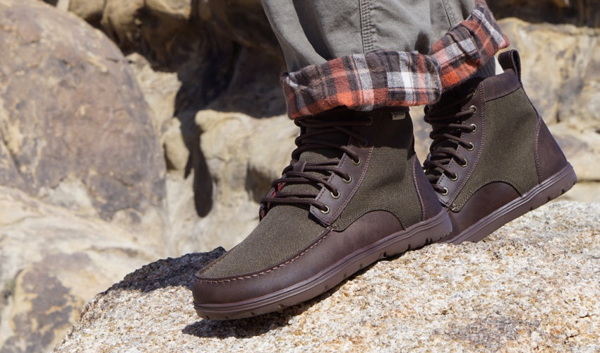 Hiker wearing the Lems Boulder Boot in Nylon Timber striding over rocky ground