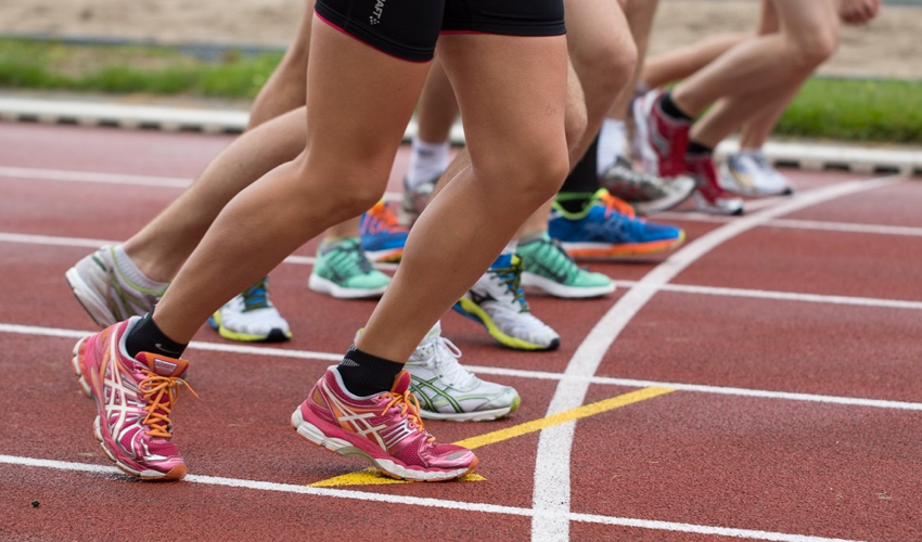The lower legs of runners in conventional athletic shoes at the start line of a track race