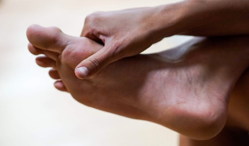 A barefooted person palpating the sole of their foot