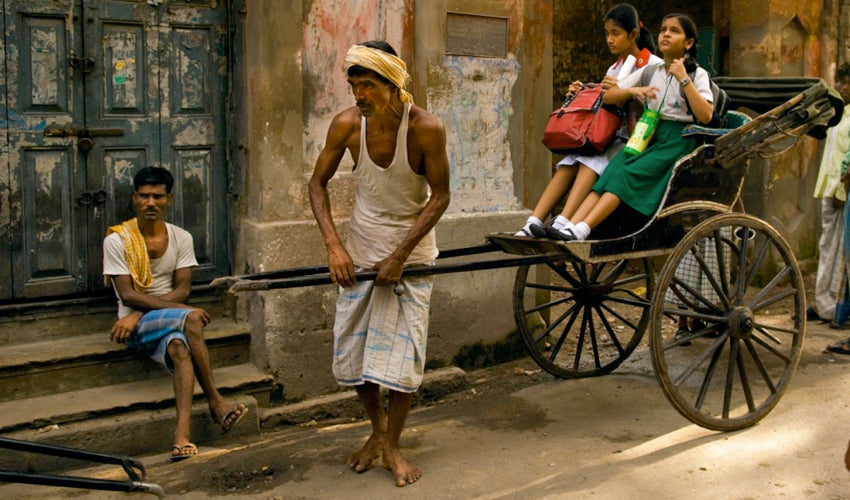 Barefooted rickshaw puller in India getting ready to launch