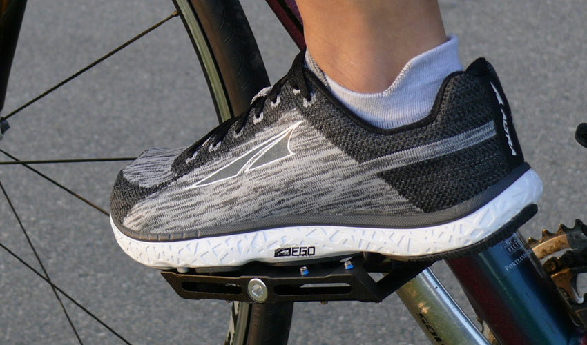 Side view of an Altra athletic shoe resting on a Black Catalyst Pedal