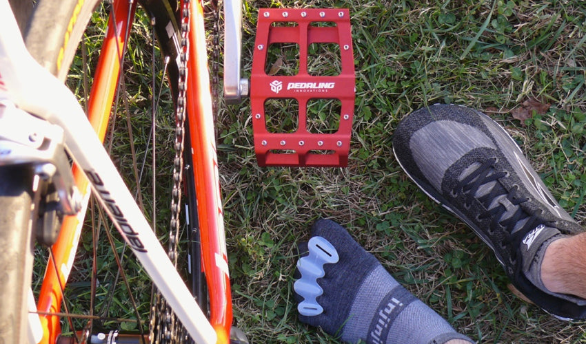 Topdown view of Catalyst Pedals in red along with feet sporting toe spacers, toe socks, and Altra athletic shoes