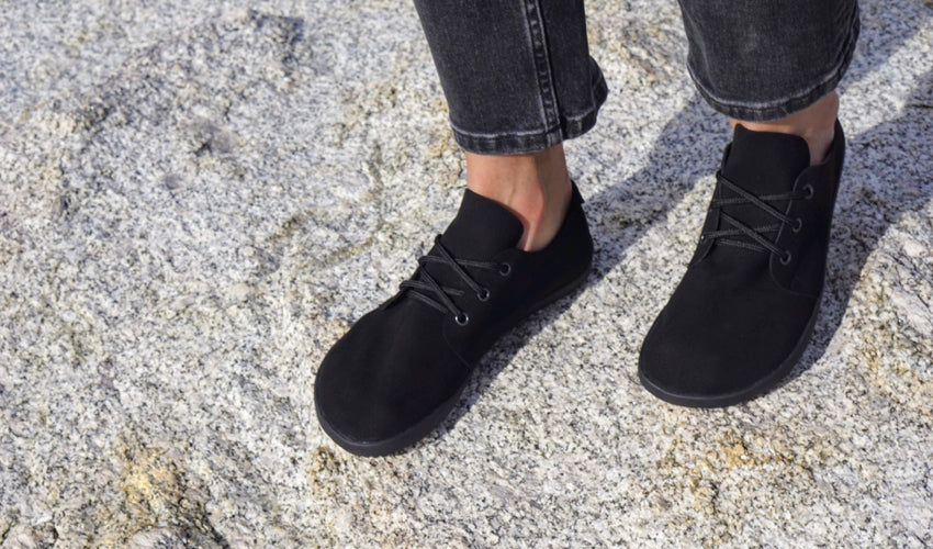 Person standing on a large stone and wearing Ahinsa Bindu Bare Black casual shoes
