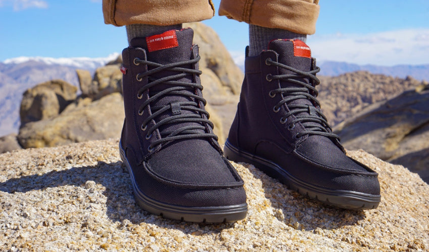 A hiker, standing on a rock with mountains in the background, wearing Lems Boulder Boots in Black