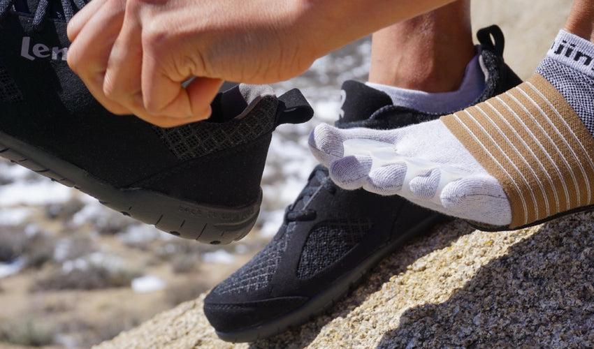 Person wearing Correct Toes, Injinji toe socks, and Strutz foot pads donning a pair of Lems Primal 2 Black shoes